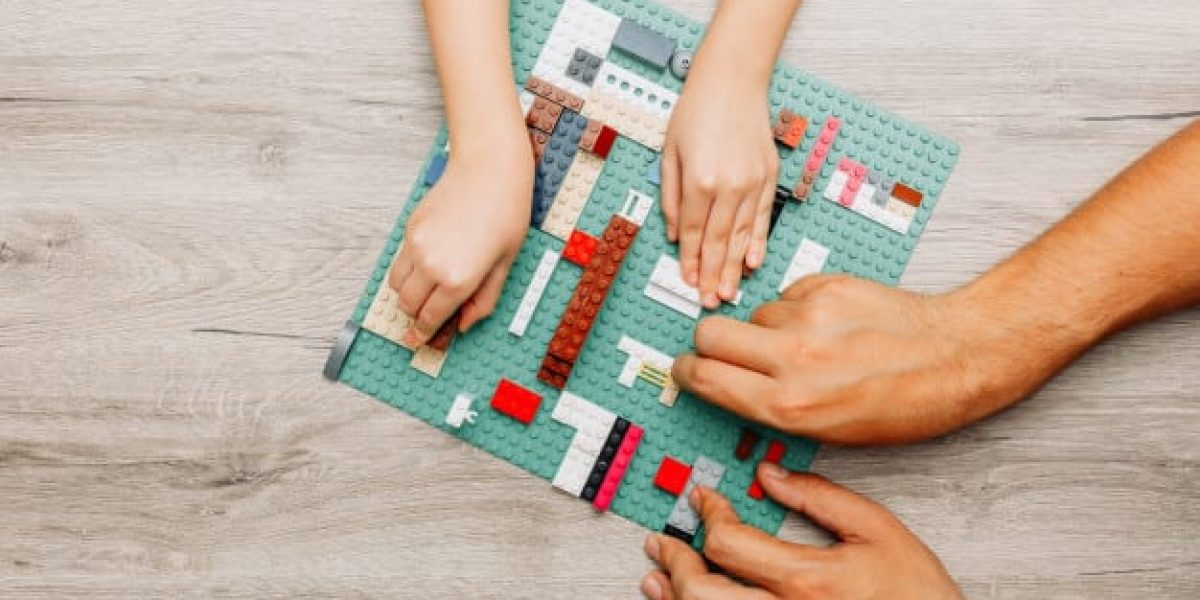 father-daughter-playing-with-legos-light-wooden_176474-2920