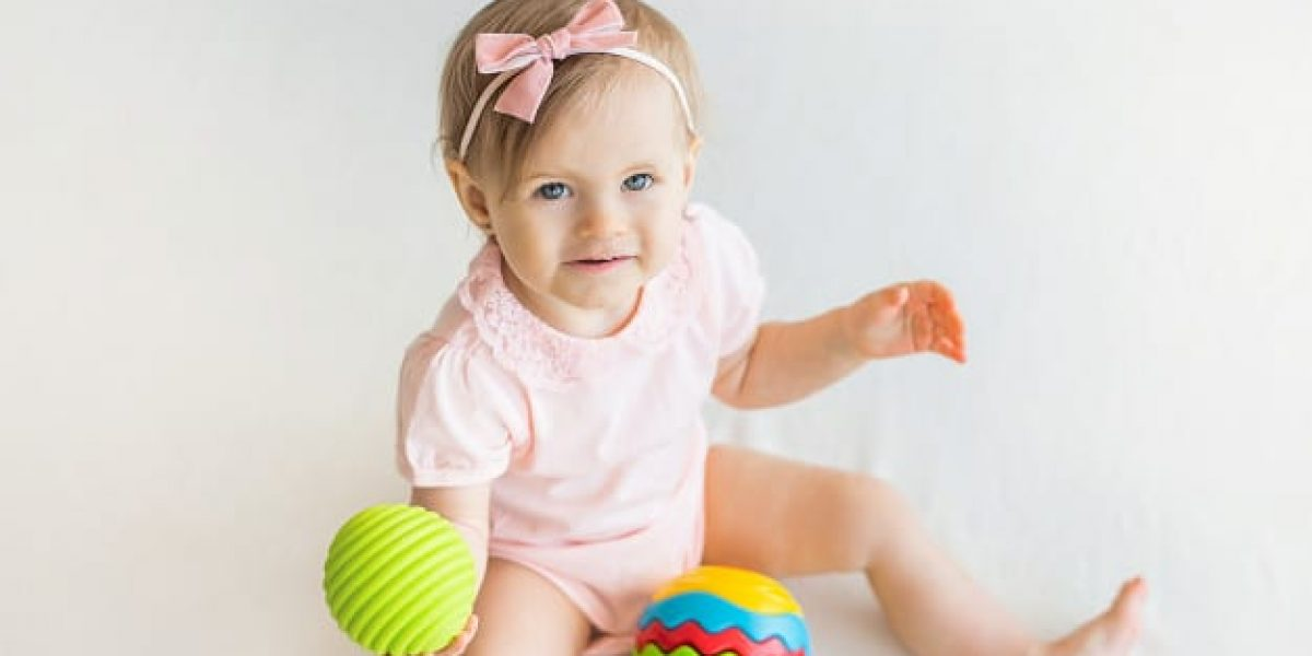 happy-nursery-baby-girl-playing-with-colorful-rubber-ball-home_215497-310