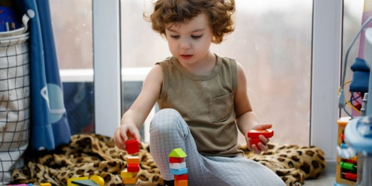 little-autistic-boy-playing-with-cubes-home_73492-652