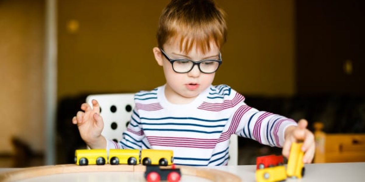 little-ginger-child-boy-glasses-with-syndrome-dawn-playing-with-wooden-railways_88194-787