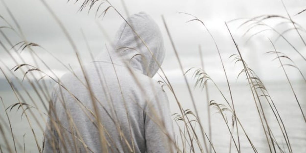 lonely-sad-person-from-with-hoodie-sitting-near-sea-thinking-about-life_181624-21979